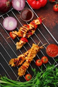 Barbecue aan het spit met saus en groenten op tafelblad weergave. barbecue-concept.