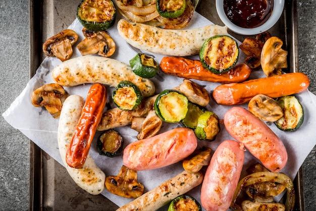Barbecue. assortiment van verschillende gegrilde vleesworsten, met groenten bbq-champignons, tomaten, courgette, uien. op een zwarte stenen tafel, op een bakplaat, met saus. copyspace