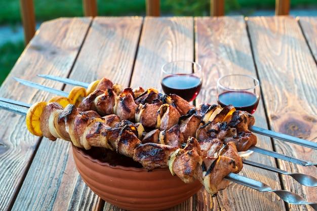 Barbecue die bij de grill en glazen rode wijn, op houten lijst wordt voorbereid.