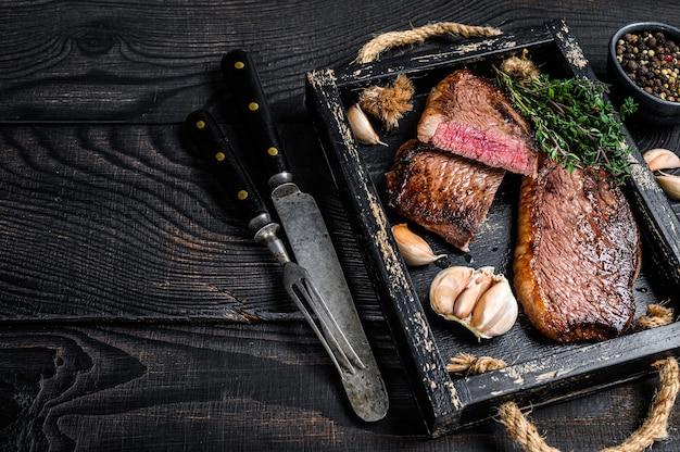 Barbecue gegrilde biefstuk of braziliaans picanha rundvlees steak in een houten dienblad op houten tafel. bovenaanzicht.