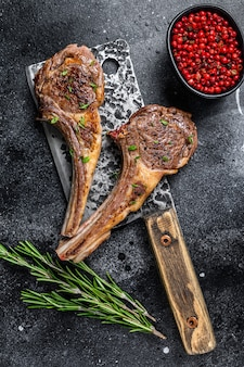 Barbecue gegrilde lamskoteletten op een slager vlees hakmes. zwarte achtergrond. bovenaanzicht.