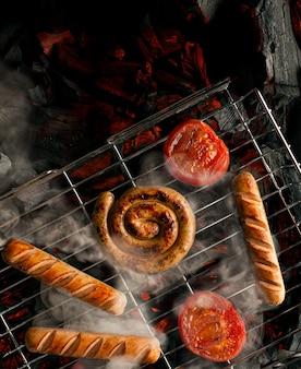Barbecue gegrilde worstjes en worstjes op de grill, brandende kolen en rook. het koken van tomaten en worstjes, worstjes op een open vuur. ã viering van 4 juli, onafhankelijkheidsdag. camping