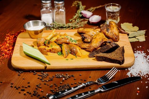 Barbecue geroosterde kippenvleugels dicht omhoog met gebraden gerechten, saus op houten achtergrond. vlees eten concept.