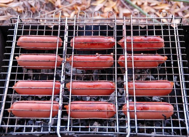 Barbecue. hotdogs gebakken in een rooster op kolen.