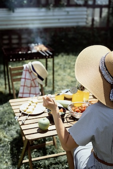 Barbecue in de achtertuin. jonge vrouw met een zomerhoed die aan tafel zit en buiten gegrilde groenten eet, achteraanzicht