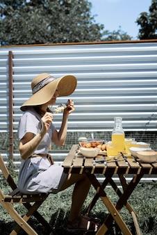 Barbecue in de achtertuin. jonge vrouw met een zomerhoed die aan tafel zit en buiten gegrilde groenten eet