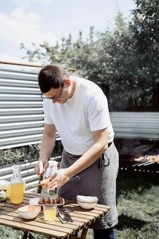 Barbecue in de achtertuin. mans handen grillen kebab en groenten op metalen spiesjes.