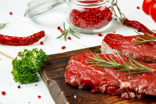 Barbecue kalfsvlees steaks met rozemarijn op houten bord