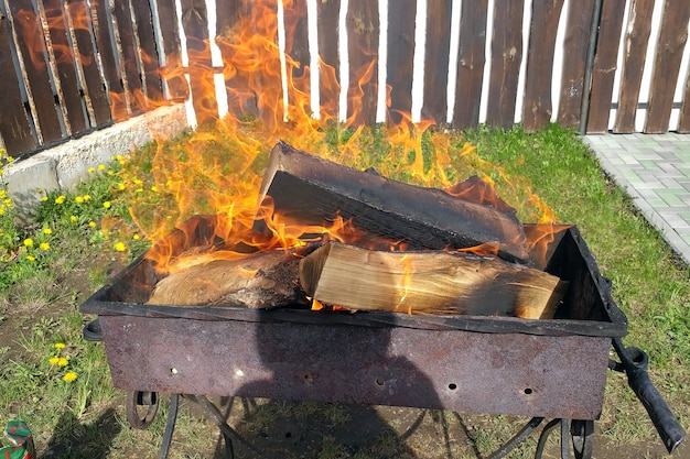 Barbecue met brandend brandhout bereiding van kolen voor kebab