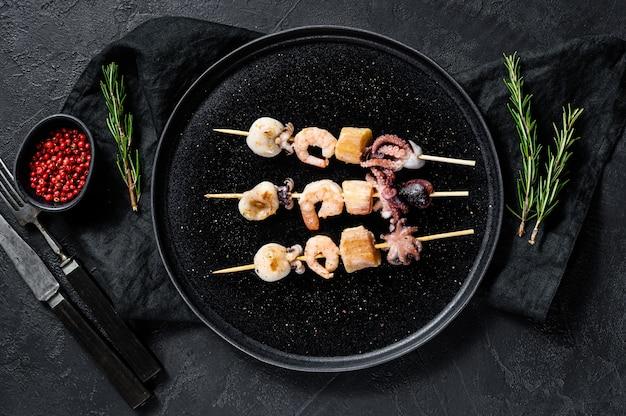 Barbecue met zeevruchten. kebab op houten spiesjes met garnalen, inktvis, inktvis en mosselen. bovenaanzicht