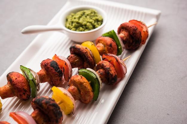 Barbecue of tandoori mushroom tikka, geserveerd in een bord met groene chutney en ketchup. selectieve focus