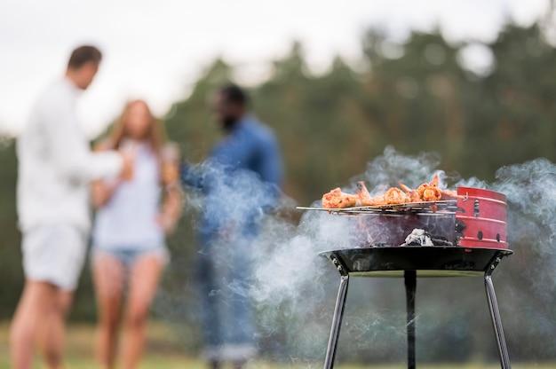 Barbecue roosteren met vrienden in gesprek