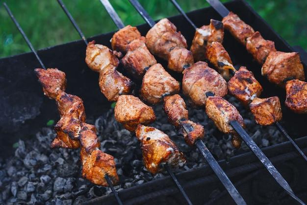Barbecue van varkensvlees wordt bereid op spiesjes op de grill