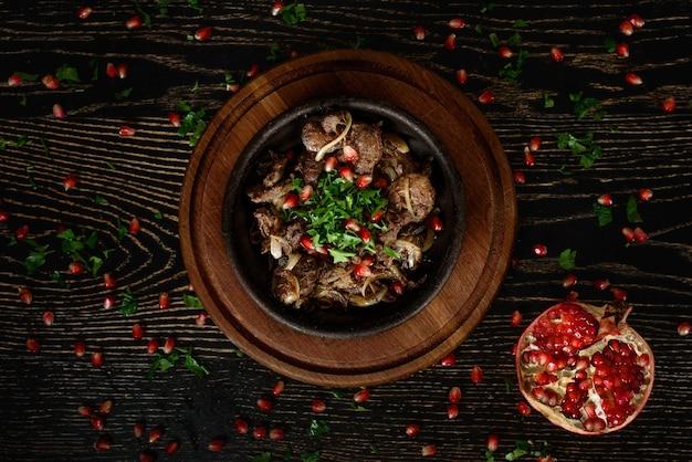Barbecue vlees met uien in een kleiplaat op een houten bord op een donkere houten tafel versierd met granaatappel en koriander. mooie tafelaankleding.
