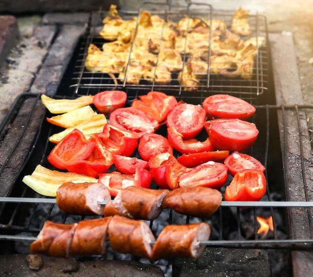 Barbecueën op het open vuur. paprika en tomaten. kip en worstjes bakken.