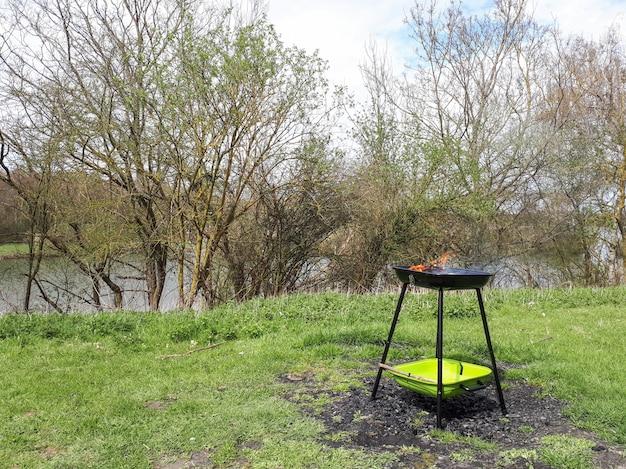 Barbecuegrill die zich bij het groene gras dichtbij de rivier bevinden