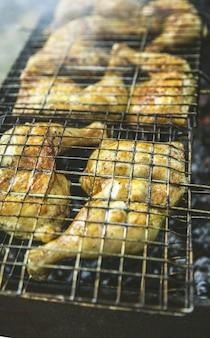 Barbecueproces in de buitenlucht. de mens doet kippengrill. het brandt van de rook.