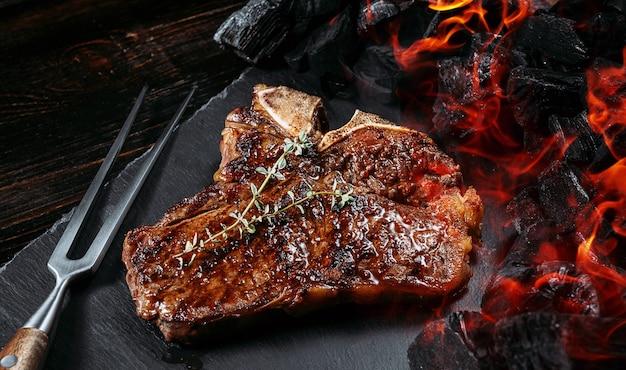 Barbecuesteak op een zwarte leisteen bord met vlees vork en grill kolen
