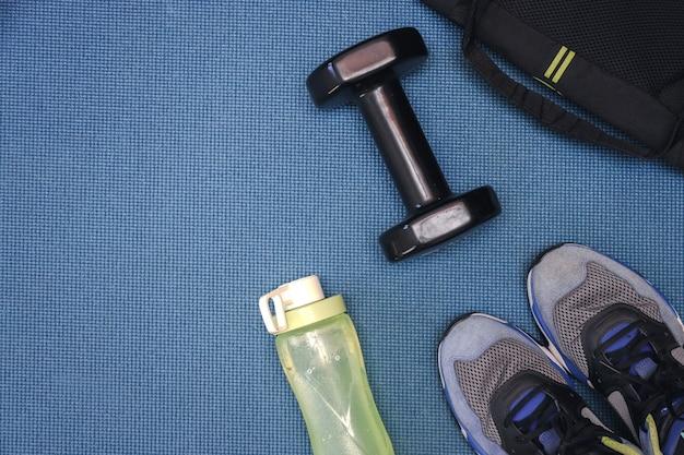 Barbell een gele waterfles, een zwarte tas en een paar schoenen op een blauwe mat voor trainingsachtergrond
