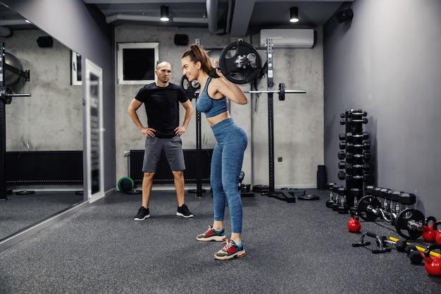 Barbell-training met gewichten. een jonge vrouw, in sportkleding en in goede conditie, doet squats en houdt een halter op haar rug. is een individuele fitnesstrainer die haar ondersteunt