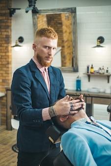 Barber shop studios. kapper scheren een bebaarde man in een kapperszaak. baard man haarstylist in de kapper bezoeken. kapperszaak.