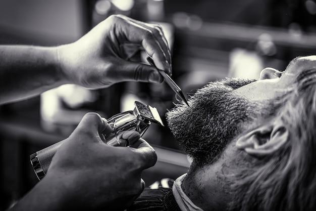 Barber werkt met een baardtondeuse. hipster-klant die kapsel krijgt. handen van een kapper met een baardclipper, close-up. zwart en wit.