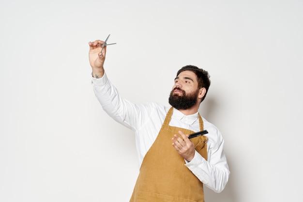Barbershop kapper man met borstelige baard en schaar met een kam