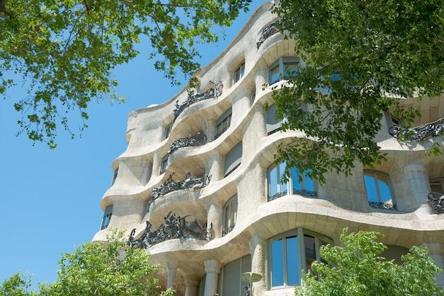 Barcelona, spanje - 21 mei 2016: gevel van casa mila met groene bomen aan de straat van barcelona, spanje. beroemd gebouw ontworpen door antoni gaudi, opgenomen in de unesco-lijst