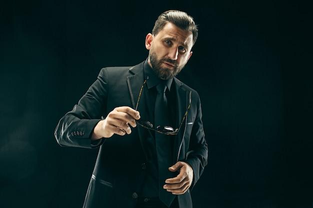 Barded man in een pak. stijlvolle zakenman op zwarte achtergrond. mooi mannelijk portret. jonge emotionele man.