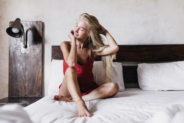 Barefoored vrouw in pyjama die haar lange haar aanraakt. mooie blanke vrouw zittend op wit vel met peinzende gezichtsuitdrukking.