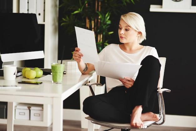 Barefoot freelancer die documenten leest op kantoor aan huis