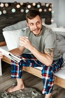 Barefoot man in pyjama met koffie zittend op bed