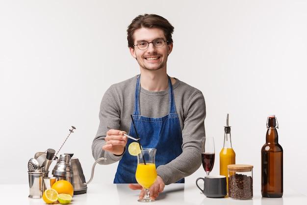 Barista, café werknemer en barman concept. het portret van de prettige jonge mens in schort bereidt tropische drank voor klant voor, vriendelijk glimlachend aangezien lever cocktail met stro en schijfje citroen