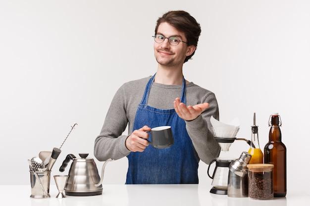 Barista, café werknemer en barman concept. hier ben je. charismatische vriendelijke jonge, bebaarde mannelijke werknemer maakte koffie voor de klant en gaf een kopje cappuccino,