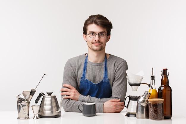 Barista, café werknemer en barman concept. hoe kan ik u helpen. vriendelijke charmante jonge mannelijke werknemer die in schort werkt, koffie voor klant maakt, dichtbij theepot, chemex en dranken staat