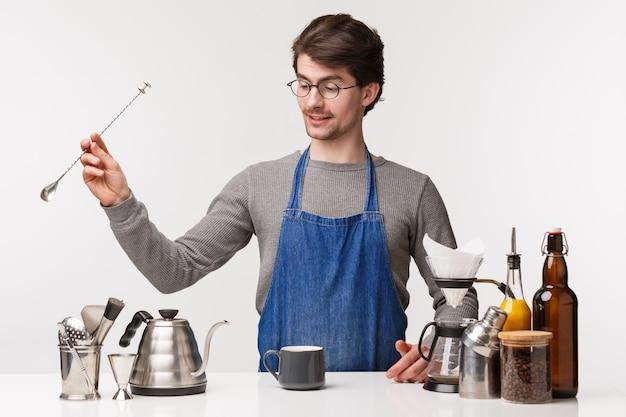 Barista, café werknemer en barman concept. knappe jonge bebaarde man restaurant werknemer in werkschort, lepel vasthouden, koffie bereiden, cappuccino of chemex maken voor klant