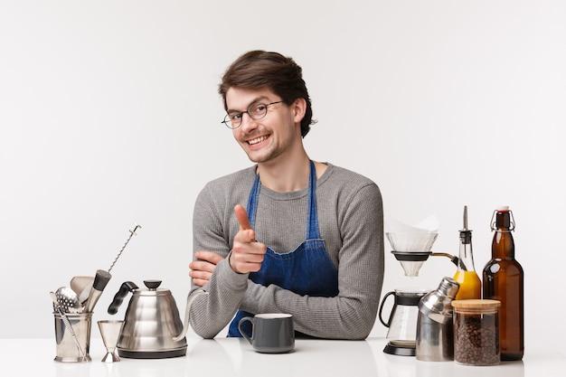 Barista, café werknemer en barman concept. portret van brutale kaukasische mannelijke werknemer die klant uitnodigt voor drank, koffie bereidt, nieuwkomer leert hoe cappuccino te maken,