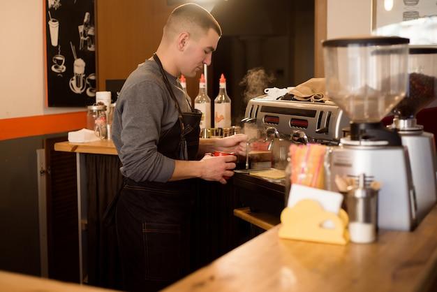 Barista die cappuccino, barman maakt die koffiedrank voorbereidt