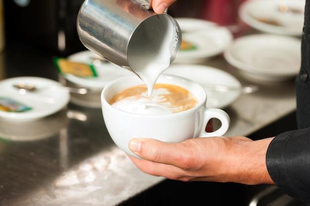 Barista die cappuccino maakt in zijn coffeeshop