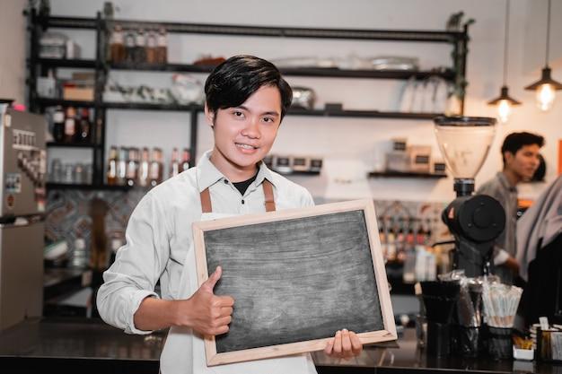 Barista die een bord en duimen omhoog houdt op tribune voor pub