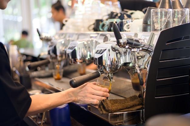 Barista die een kopje koffie maakt door de koffiemachine in het café