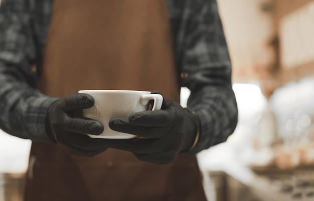 Barista die een witte kop met vers gezette koffie houdt.