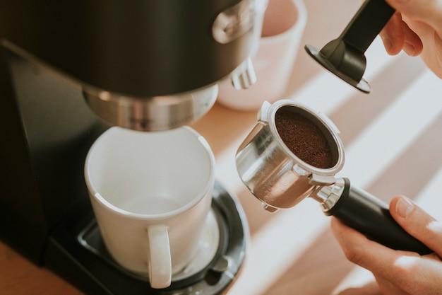 Barista die gemalen koffie in een filterkoffie van machine drukt