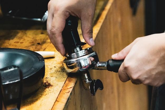 Barista die in een koffiewinkel werken, sluit omhoog van barista drukt gemalen koffie gebruikend stamper