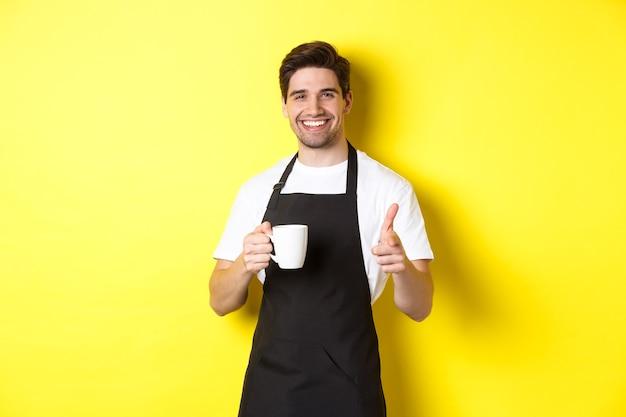 Barista die koffie en wijzend vingerpistool op camera brengt, die zich in zwarte schort tegen gele achtergrond bevindt.