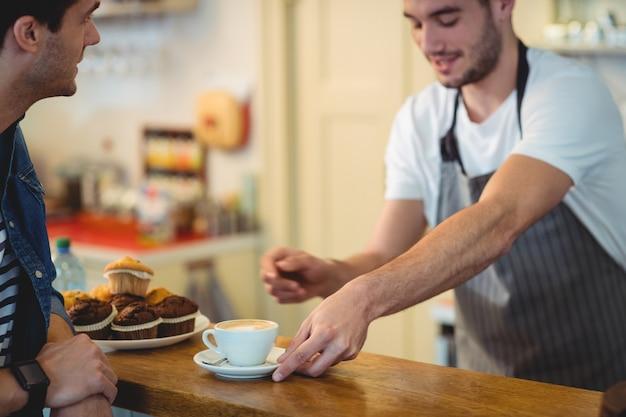 Barista die koffie geven aan klant bij koffie