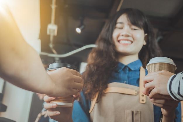 Barista die koffie geven aan klant in haar winkel. selectieve aandacht