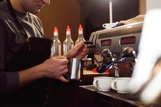 Barista die koffie maakt die een koffiemachine, een gastvrijheid en een hete drankconcept met behulp van.