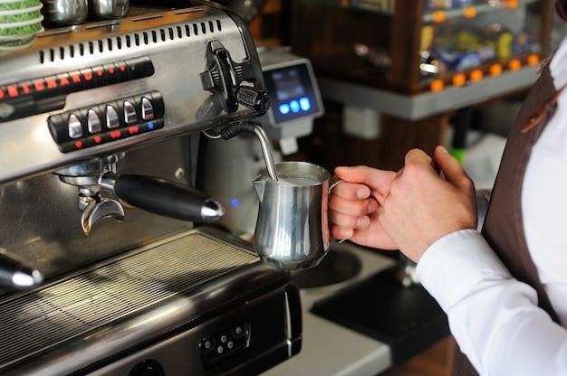 Barista die koffie maakt. melk klaarmaken voor cappuccino