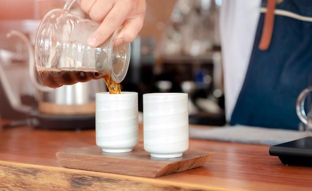 Barista die koffie met het gieten maakt